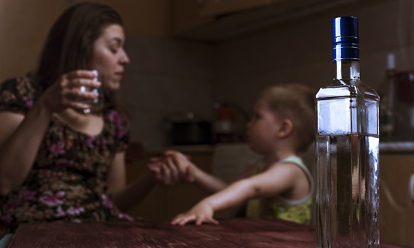 Woman drinking alcohol while talking to small child