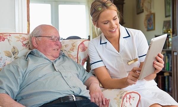 nurse and patient view laptop