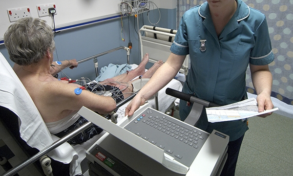 Healthcare assistant performing an ECG on a patient