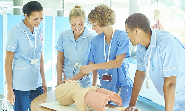 Three nurses undergoing training by a fourth nurse