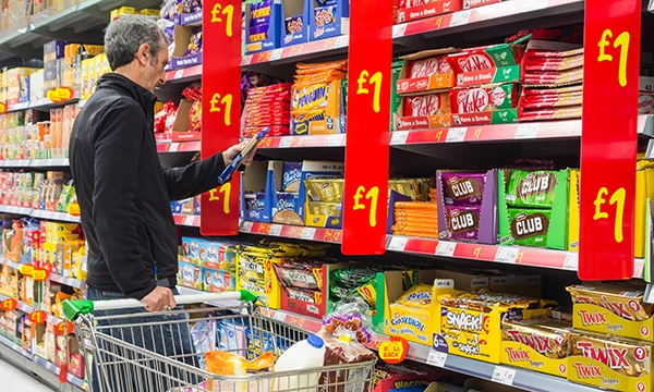 Man in supermarket browsing biscuit section