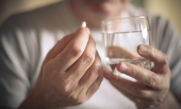 Close up of someone preparing to take a pill with a glass of water