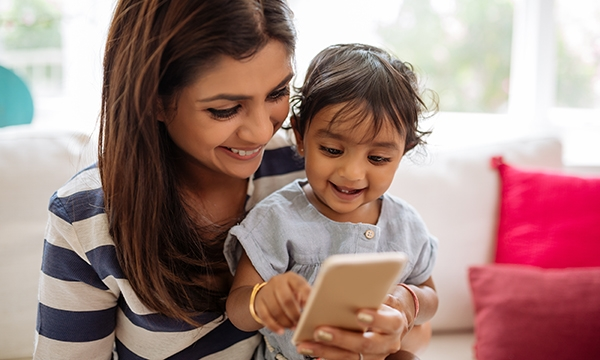 Woman with a small child looking at a smartphone