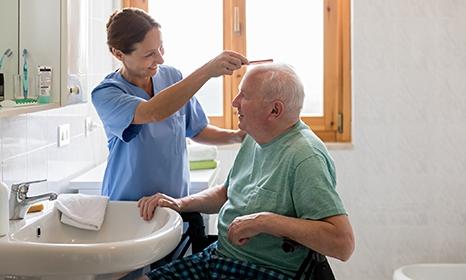 Nurse combing an older patient's hair