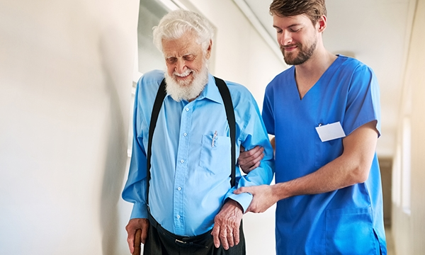 A nurse helps an elderly man walking down a corridor