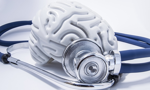 Model of a brain next to a stethoscope